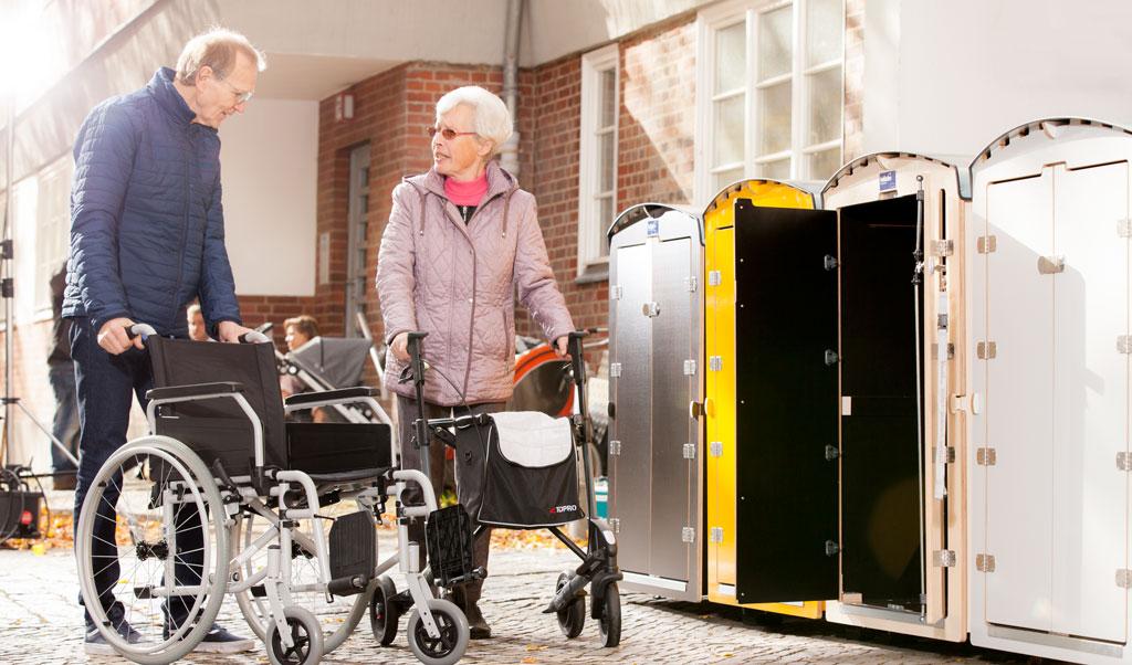 Zwei Rentner bedienen die Rollatorbox rollabo L. Vier Rollatorboxen wurden platziert