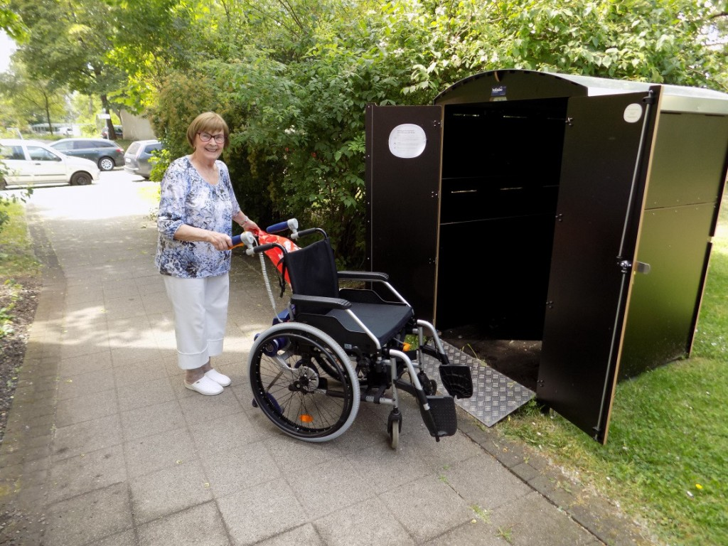 Frau Gottwald steht mit ihrem Rollstuhl vor einer Rollabo Rollatorbox und schiebt den Rollstuhl hinein